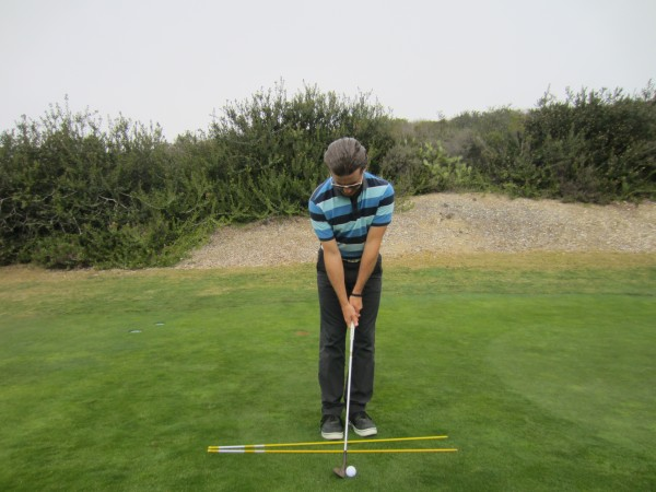 Note the open stance, square club face, and head position forward of the golf ball.