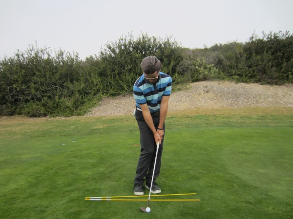 Note the forward handle, open club face and open shoulders parallel to the feet line.