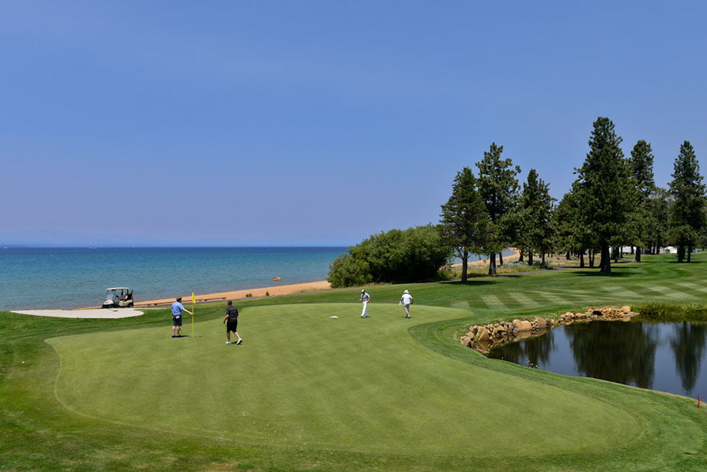 A group putts out on the 18th green next to Lake Tahoe.